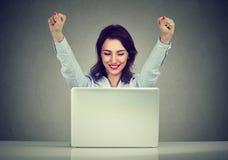 Den lyckade kvinnavinnaren med armar lyftte att se bärbara datorn royaltyfri fotografi