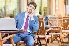 Den lyckade mannen räcker upp utomhus- på kafét Fotografering för Bildbyråer