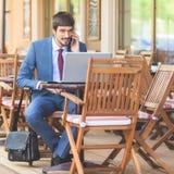 Den lyckade mannen räcker upp utomhus- på kafét Royaltyfria Bilder
