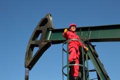 Den lyckade olje- arbetaren på arbetsvisningen tummar upp. Arkivbild