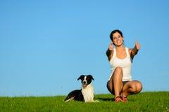 Den lyckade sportiga kvinnan som tar öva, vilar med hennes hund fotografering för bildbyråer