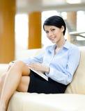 Den lyckade unga affärskvinnan vilar på sofaen royaltyfria bilder