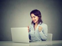 Den lyckade vinnaren för den unga kvinnan med armar lyftte att se bärbar datorsammanträde på skrivbordet arkivbild