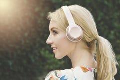 Den lycklig unga nätta kvinnlign lyssnar till musik på hörlurar som ler och arkivfoto