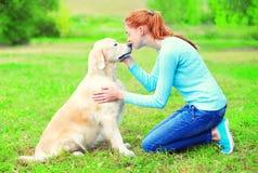 Den lyckliga ägarekvinnan är kyssande hennes golden retrieverhund parkerar in arkivbilder