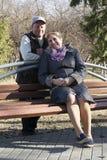 Den lyckliga äldre familjen sitter på en bänk i parkera Royaltyfria Bilder