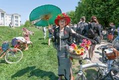 Den lyckliga äldre kvinnan i gammalt mode klär med cykeln som poserar Retro kryssning för utomhus- festival Arkivfoto
