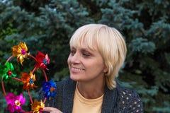 Den lyckliga äldre kvinnan ler och spelar med propellern Arkivbild