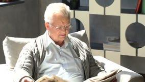 Den lyckliga äldre mannen sitter i en stol och en läsning en tidning i en modern lägenhet lager videofilmer