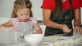 Den lyckliga älska familjen förbereder bagerit tillsammans Moder- och barndotterflickan lagar mat kakor och har gyckel in lager videofilmer