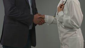 Den lyckliga återställda mannen uttrycker tacksamhet till doktorn som skakar händer arkivfilmer