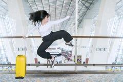 Den lyckliga affärskvinnan hoppar i flygplatsen arkivbilder