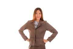 Den lyckliga affärskvinnan i brun dräkt ler på och beväpnar akimbo Royaltyfri Foto