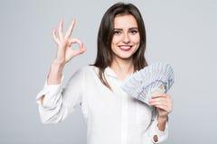 Den lyckliga affärskvinnan som rymmer oss reko pengar och att göra en gest för dollar, undertecknar över vit bakgrund fotografering för bildbyråer