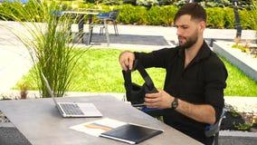 Den lyckliga affärsmannen arbetar utanför med bärbara datorn och att tycka om med virtuell verklighetexponeringsglas stock video