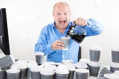Den lyckliga affärsmannen dricker för mycket kaffe Royaltyfria Bilder