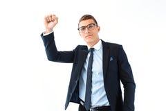 Den lyckliga affärsmannen i exponeringsglas och dräkt visar en gest av framgång arkivfoton