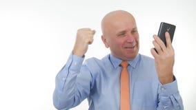 Den lyckliga affärsmannen Make Enthusiastic Winner gör en gest läsa goda nyheter på mobiltelefonen royaltyfri foto