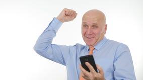Den lyckliga affärsmannen Make Enthusiastic Winner gör en gest lästa goda nyheter på mobil royaltyfria foton