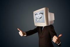 Den lyckliga affärsmannen med en datorbildskärm och en smiley vänder mot Arkivbilder