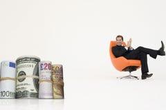 Den lyckliga affärsmannen som ser pengar, rullar föreställa tillväxt i internationell affär Royaltyfri Foto