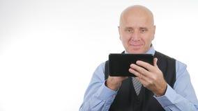 Den lyckliga affärsmannen Working med ett minnestavlaleende tillfredsställde arkivfoto