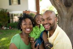 Den lyckliga afrikansk amerikanfamiljen med deras behandla som ett barn Fotografering för Bildbyråer