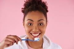 Den lyckliga afrikansk amerikankvinnan borstar tänder royaltyfri fotografi