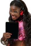 Den lyckliga afrikansk amerikankvinnan som lyssnar till musik med headphonen, fäste till minnestavlaPC:n Royaltyfria Bilder