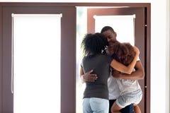 Den lyckliga afrikansk amerikanmannen ankom hem, att omfamna för familj royaltyfri foto