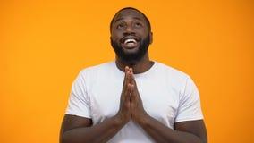 Den lyckliga afrikansk amerikanmannen som rymmer händer för, ber och ser upp och att välsigna guden arkivfilmer