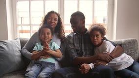 Den lyckliga afrikanska familjen med barn vinkar händer som ser kameran lager videofilmer