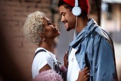 Den lyckliga afro- amerikanska mannen i heaphones och hans mörker flådde kvinnlig med den lockiga frisyren står nästan, ser fotografering för bildbyråer