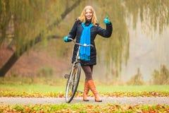 Den lyckliga aktiva kvinnan med cykeln i höst parkerar Royaltyfri Foto