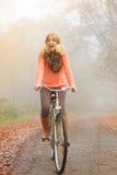 Den lyckliga aktiva kvinnaridningcykeln i höst parkerar Royaltyfria Foton