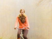 Den lyckliga aktiva kvinnaridningcykeln i höst parkerar Arkivbilder
