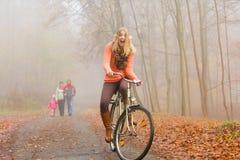 Den lyckliga aktiva kvinnaridningcykeln i höst parkerar Arkivfoto