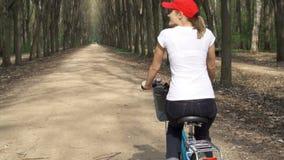 Den lyckliga aktiva sportive unga kvinnan i rött lock som cyklar till och med soligt, parkerar på dag för sommar` s långsam rörel stock video