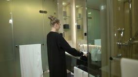 Den lyckliga arabiska kvinnan ser i spegel i badrummet hemma eller hotell Den europeiska blonda muslimflickan med blåa ögon tar b lager videofilmer