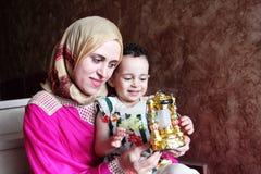 Den lyckliga arabiska muslimmodern med hennes behandla som ett barn flickan med den ramadan lyktan arkivbilder