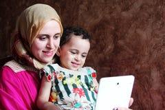 Den lyckliga arabiska muslimmodern med hennes behandla som ett barn flickan som tar selfie Arkivbild