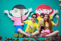 Den lyckliga asia familjen med barn visar handen Arkivbilder