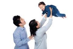 Den lyckliga asia familjen med behandla som ett barn flickan kastar upp royaltyfri foto