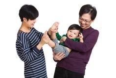 Den lyckliga asia familjen som spelar med, behandla som ett barn pojken arkivbilder