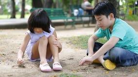 Den lyckliga asiatet lurar att spela sand i en parkera, Bangkok Thailand lager videofilmer