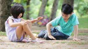 Den lyckliga asiatet lurar att spela sand i en parkera, Bangkok Thailand arkivfilmer