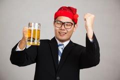 Den lyckliga asiatiska affärsmannen med partihatten får berusad med öl Arkivbild