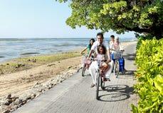 Den lyckliga asiatiska familjridningen cyklar i den härliga morgonen på Arkivfoto