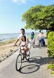 Den lyckliga asiatiska familjridningen cyklar i den härliga morgonen på Royaltyfri Bild