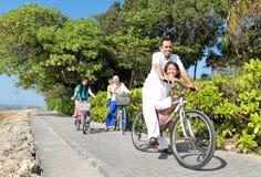 Den lyckliga asiatiska familjridningen cyklar i den härliga morgonen på Fotografering för Bildbyråer